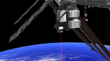 An artist's rendering shows the Optical Payload for Lasercomm Science (OPALS) laser beaming down to Earth from the International Space Station.