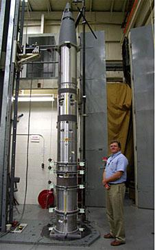 Phil Eberspeaker stands next to a sounding rocket payload