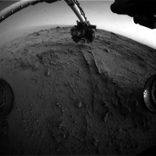 This image from the rover's front Hazard Avoidance Camera (Hazcam) on that sol shows the position of the turret during that process, with the Alpha Particle X-ray Spectrometer (APXS) instrument placed close to the target rock.
