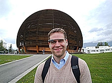 A man wearing glasses stands in a field in front of a large half-sphere structure
