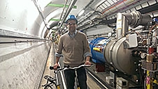 A man stands beside a bicycle in a large tunnel