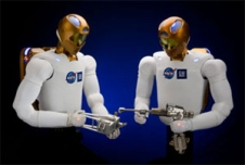 Two Robonaut models hold tools