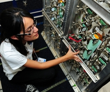 Krystal Vasquez, a chemistry major at the University of California, Riverside, assists in the installation of the Whole Air Sampler instrument on NASA's DC-8 flying laboratory.