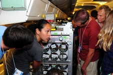 Josette Marrero, a Ph.D. candidate in the Rowland-Blake Lab at UC Irvine, explains the installation of the Whole Air Sampler on board NASA's DC-8 to Student Airborne Research Program participants.