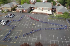 people form the outline of a space shuttle in a parking lot