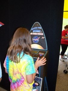 A girl stands on the solar system scale to find out how much she would weigh on Jupiter.
