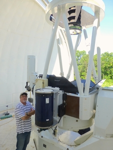 man standing near telescope