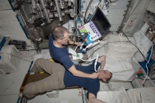 NASA astronaut Tom Marshburn assists Canadian Space Agency astronaut Chris Hadfield, with an Ultrasound 2 scan in the Columbus Module of the International Space Station.