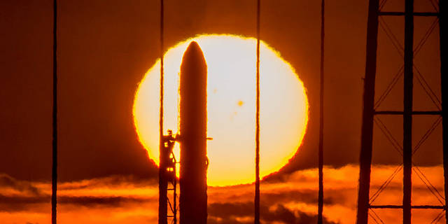 Antares rocket at Wallops with sun in background