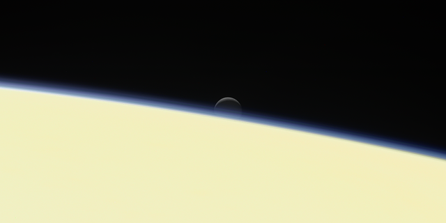 moon Enceladus behind Saturn