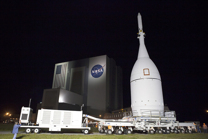 At NASA's Kennedy Space Center in Florida, the agency's Orion spacecraft pauses in front of the spaceport's iconic Vehicle Assembly Building as it is transported to Launch Complex 37 at Cape Canaveral Air Force Station. After arrival at the launch pad, United Launch Alliance engineers and technicians will lift Orion and mount it atop its Delta IV Heavy rocket.