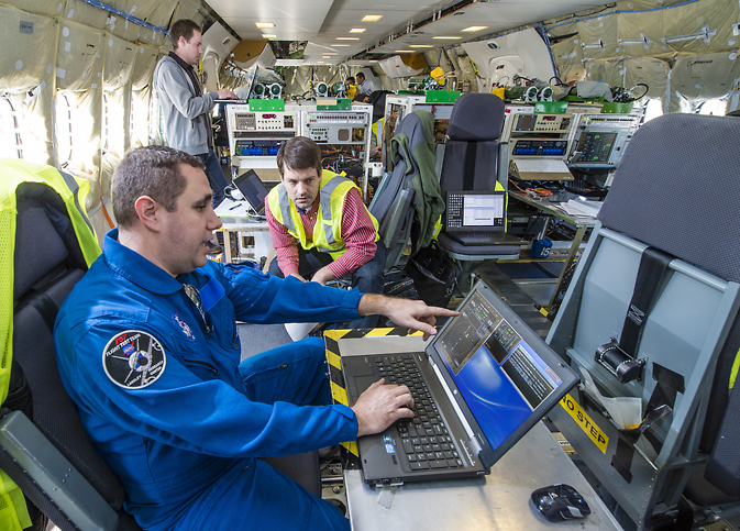 NASA flight engineer Roy Roper (left) reviews laptop displays showing the ASTAR data with Boeing principal investigator
