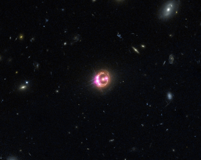 Multiple images of a distant quasar known as RX J1131-1231 are visible in this combined view from Chandra (pink) and Hubble (red, green, and blue)