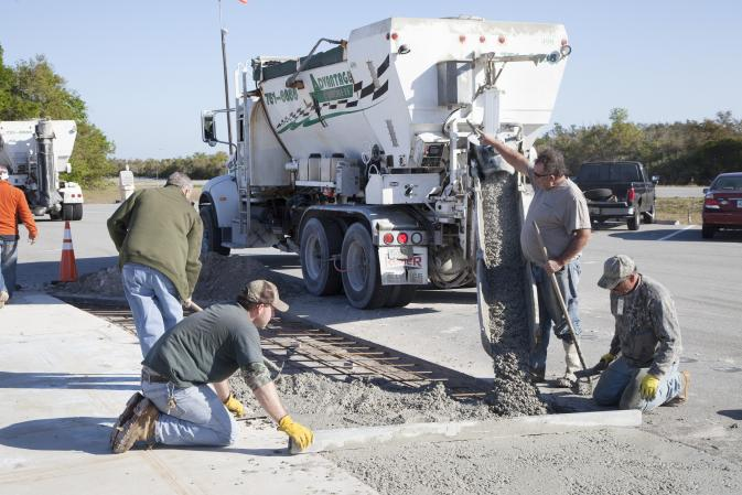 Workers pour a special concrete mixture that includes spent sandblasting media