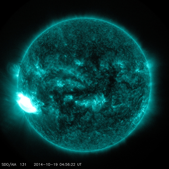A solar flare surges off the lower left hand of the sun in this image captured by NASA's SDO on Oct. 19, 2014.