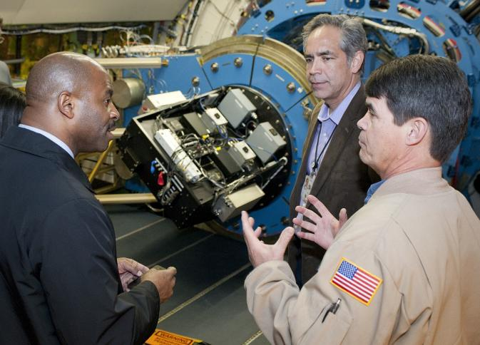 NASA Dryden electronics technician Jim Mills explains details of the High-speed Imaging Photometer for Occultation, or HIPO, mounted on the SOFIA observatory's infrared telescope to NASA education chief and former space shuttle astronaut Leland Melvin during his tour of the Dryden Aircraft Operations Facility with center director David McBride. Image credit: NASA