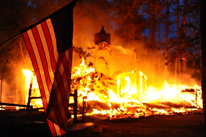 U.S. flag hangs in front of a burning structure in Black Forest, Colo., June 12, 2013.