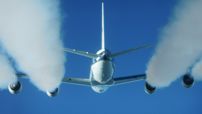 Puffy white exhaust contrails stream from the engines of NASA's DC-8 flying laboratory during tests of alternative jet engine fuel emissions.