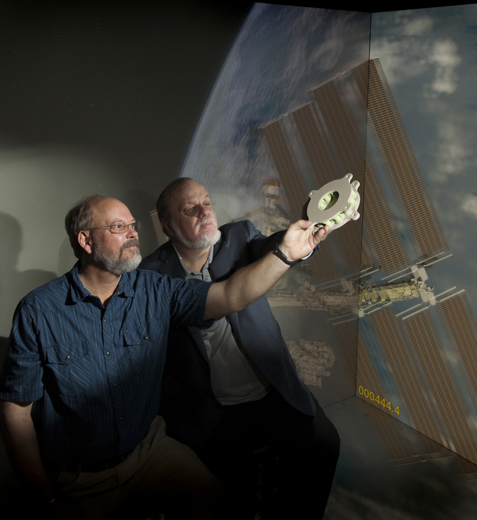 Goddard technologists hold a 3-D-printed battery-mounting plate developed specifically for a sounding-rocket mission.