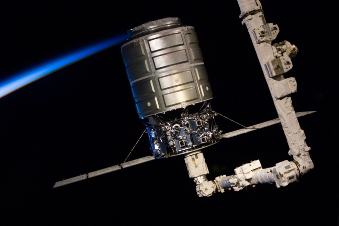 This medium close-up view, photographed by one of the Expedition 37 crew members, shows the first Cygnus commercial cargo spacecraft built by Orbital Sciences Corp. attached to the end of the robotic arm (AKA Canadarm2) on the International Space Station after the two spacecraft converged at 7:01 a.m. EDT on Sept. 29, 2013.
