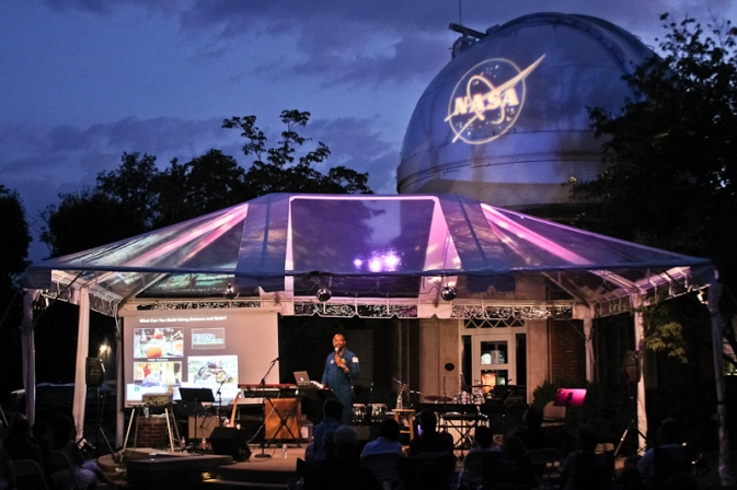 A tent covering a platform where an astronaut is speaking to students. The NASA insignia is illuminated on the side of an observatory in the background