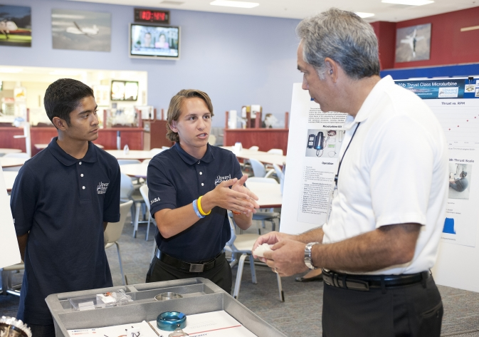 Daniel Gutierrez and Michael Arreola, high school students in the Department of Education's Upward Bound summer program, explain their micro-turbine project to David McBride, director of NASA's Dryden Flight Research Center