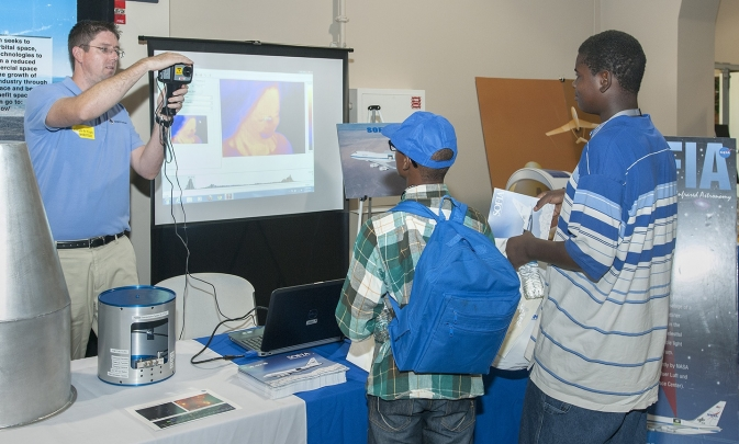 Shaun Smith, a flight projects education specialist at the NASA Dryden-affiliated AERO Institute in Palmdale, Calif., demonstrates imagery from an infrared camera to two student attendees at the 2013 Salute to Youth.