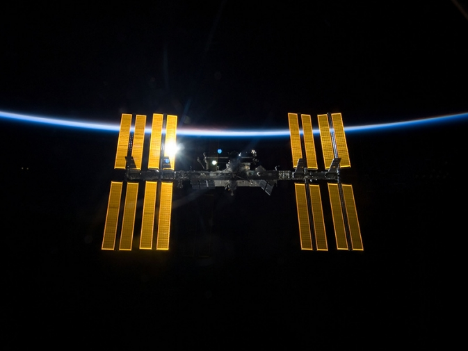 The International Space Station, backdropped by the blackness of space and the thin line of Earth's atmosphere.