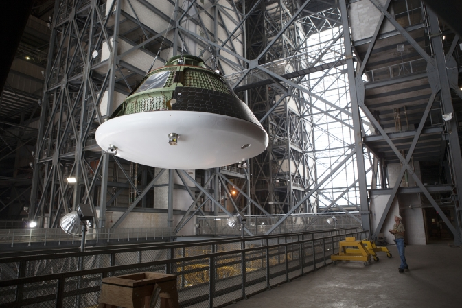 At NASA's Kennedy Space Center in Florida, the Orion ground test vehicle has been lifted high in the air by crane in the transfer aisle of the Vehicle Assembly Building.