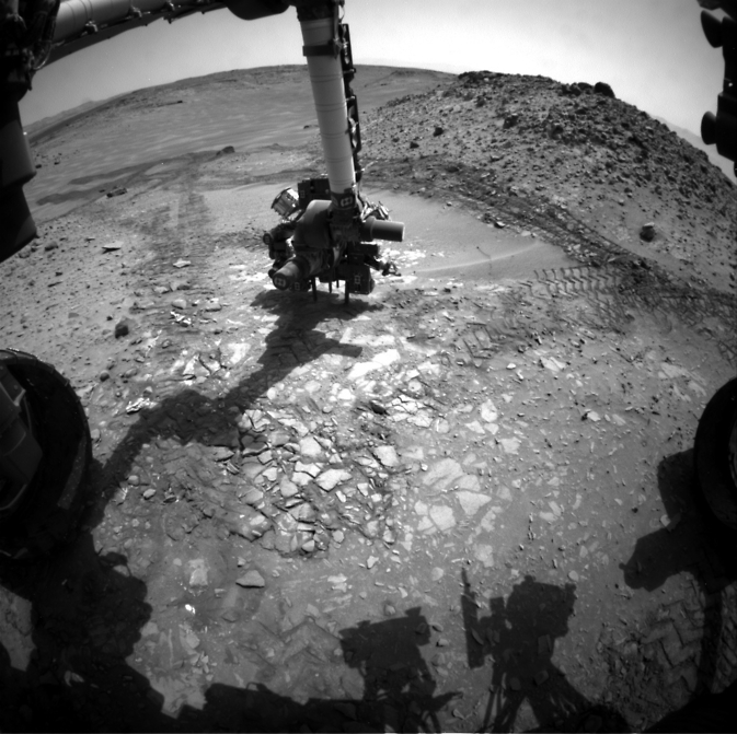 This image from the front Hazcam on NASA's Curiosity Mars rover shows the rover's drill in place during a test