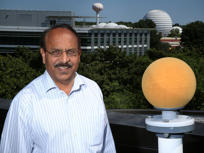 Qamar Shams, who invented the Extreme Low Frequency Acoustic Measurement System with colleague Allan Zuckerwar, stands next to one of the system's windscreen-encased microphones on the rooftop of a building at NASA's Langley Research Center.
