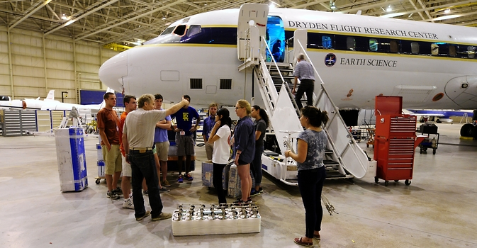 Professor Donald Blake of the University of California—Irvine outlines procedures for installation of air canister racks on NASA's DC-8 flying laboratory to students participating in NASA's 2014 Student Airborne Research Program.