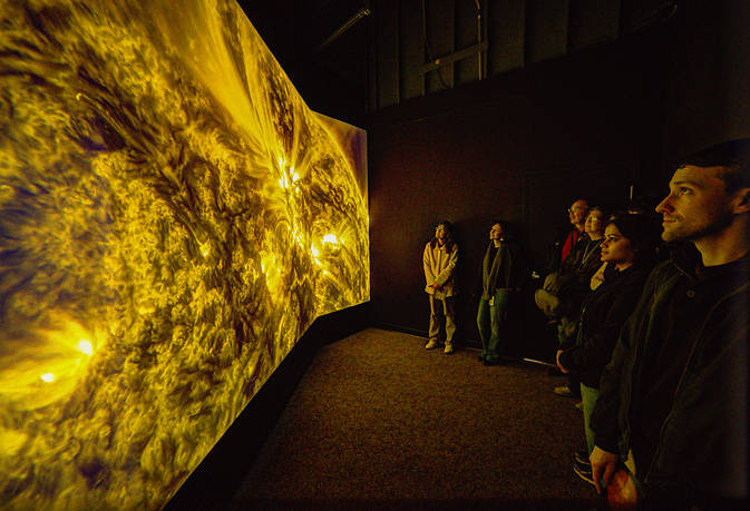 Visitors stand in front of the Solarium display.