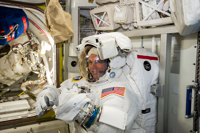 NASA astronaut Reid Wiseman checks his spacesuit in preparation for the first Expedition 41 spacewalk.