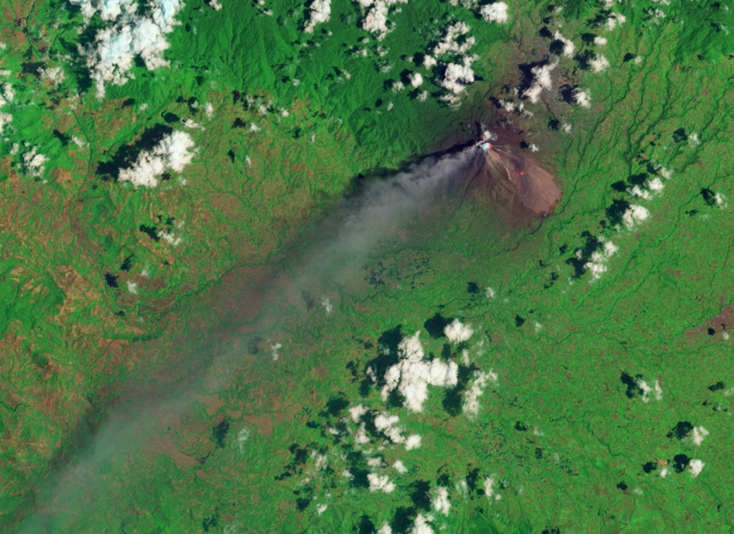 satellite view of volcano with smoke plumes against green terrain