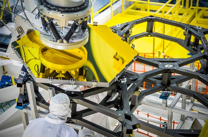 The robotic arm lifts and lowers a golden James Webb Space Telescope flight spare primary mirror segment onto a test piece of backplane at NASA's Goddard Space Flight Center in Greenbelt, Md.
