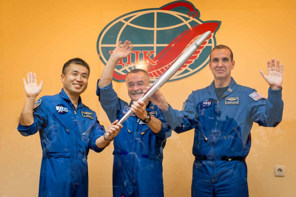 Expedition 38 Flight Engineer Koichi Wakata of the Japan Aerospace Exploration Agency, left, Soyuz Commander Mikhail Tyurin of Roscosmos, and, Flight Engineer Rick Mastracchio of NASA, right, smile and wave as they hold an Olympic torch that will be flown with them to the International Space Station, during a press conference held Wed., Nov. 6, 2013, at the Cosmonaut hotel in Baikonur, Kazakhstan.