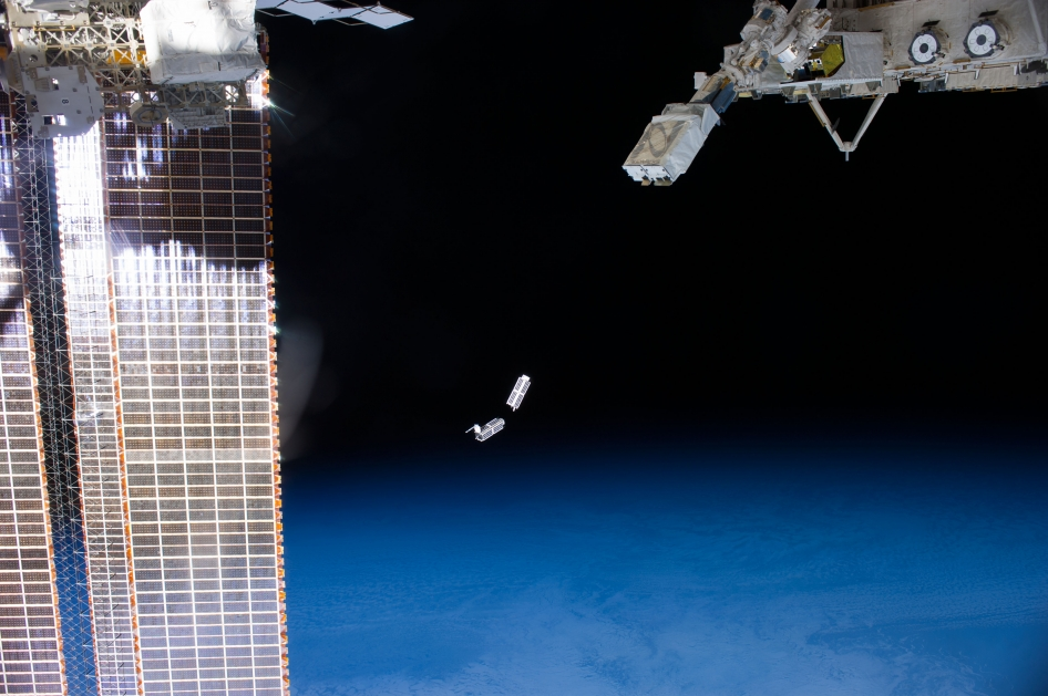 A set of NanoRacks CubeSats is photographed by an Expedition 38 crew member after the deployment by the NanoRacks Launcher attached to the end of the Japanese robotic arm.