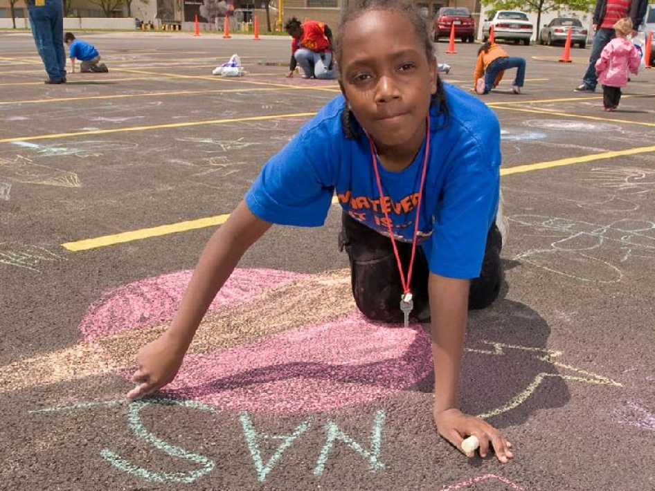 "A young boy writes ""NASA"" in chalk at NASA Glenn's open house"