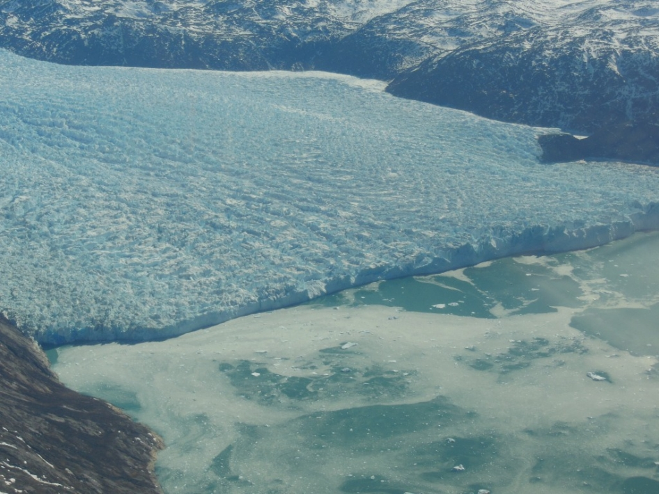 A heavily crevassed glacier's calving front in a fjord in southwest Greenland.
