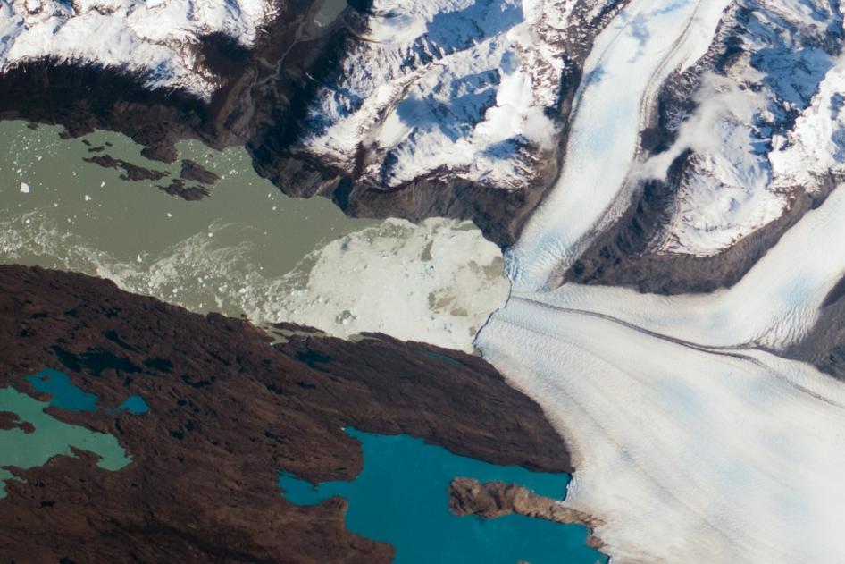 This photograph by an astronaut on the International Space Station highlights the snout of the Upsala Glacier (49.88°S, 73.3°W) on the Argentine side of the North Patagonian Icefield. Ice flow in this glacier comes from the north (right in this rotated image). Dark lines of rocky debris (moraine) within the ice give a sense of the slow ice flow from right to left.