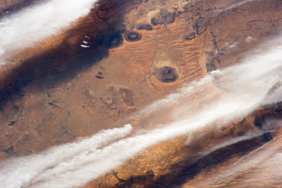 This photograph of cloud bands over southern Mauritania was taken from the International Space Station with an oblique angle such that the cloud shadows are a prominent part of the view.