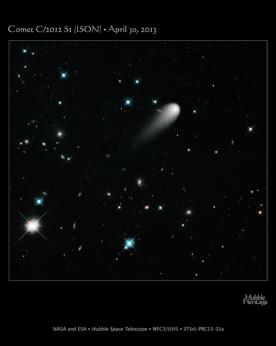 comet ISON swims amonst a scattering of stars and galaxies
