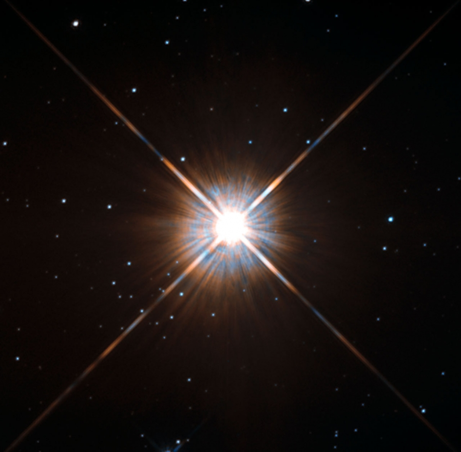 brilliant blue-white star with x-shaped lens flare
