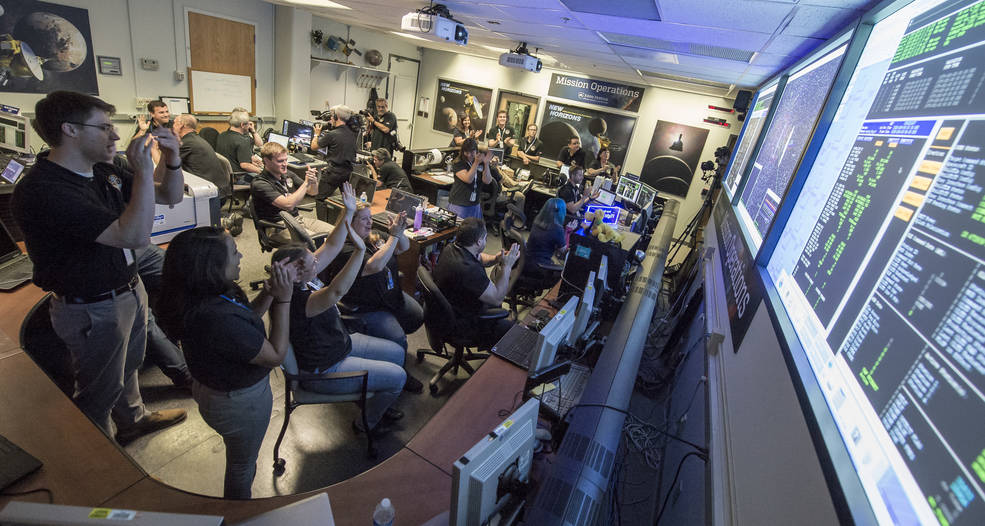 """Miembros del equipo de la msisión de New Horizons celebran la """"llamada a casa"""" de New Horizons."""