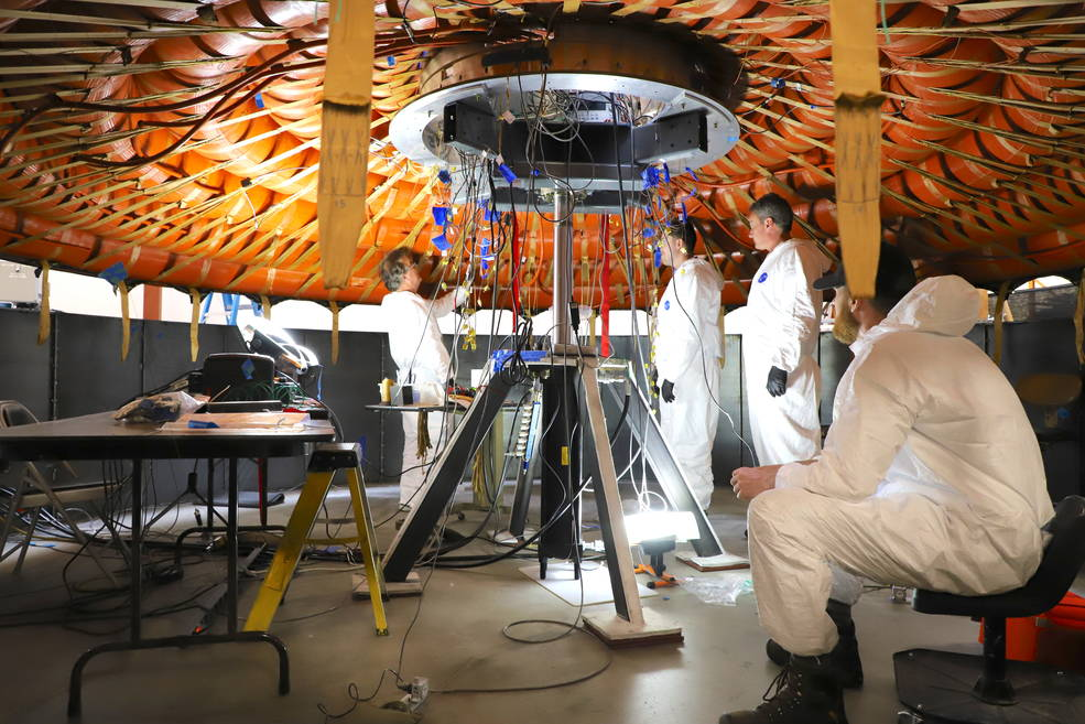 People working with heat shield inflatable structure.
