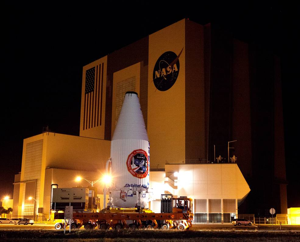 Encapsulated Cygnus Moves Past Vehicle Assembly Building