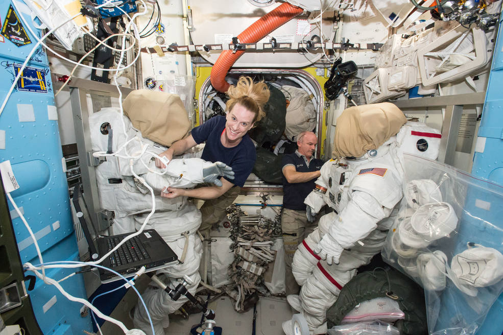 Astronauts Kate Rubins and Jeff Williams inside airlock, examining spacesuits