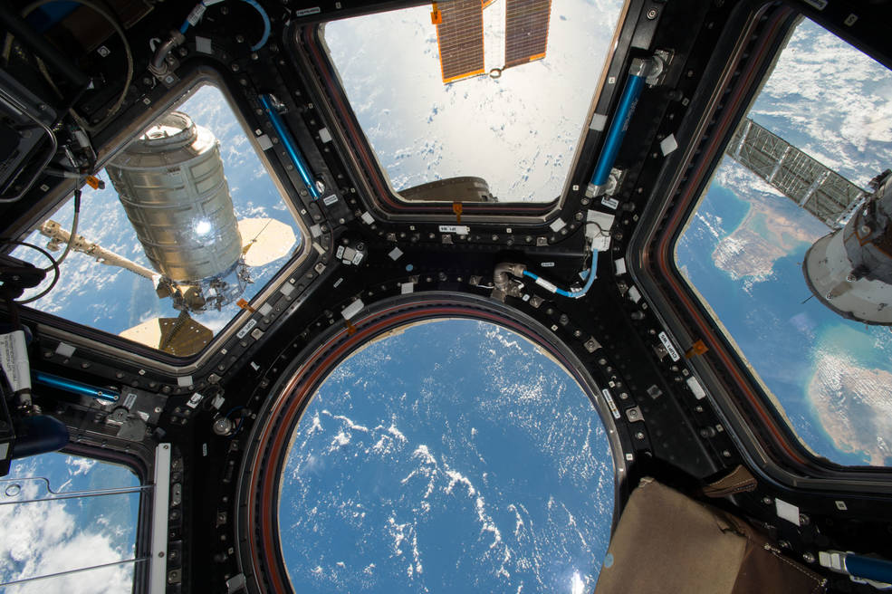 View from Cupola windows on space station with Cygnus cargo ship visible at left and Earth below