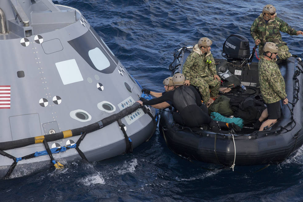 U.S. Navy divers and other personnel in a Zodiac boat secure a harness around a test version of the Orion crew module